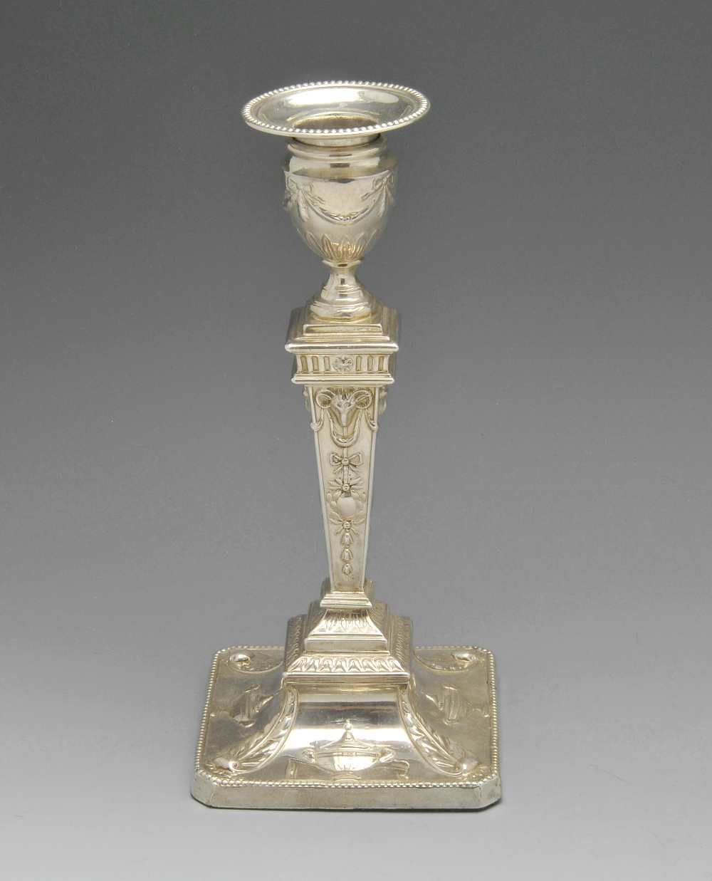Lot 61 - An Edwardian silver mounted candlestick of Neoclassical style, the urn shaped socket raised upon