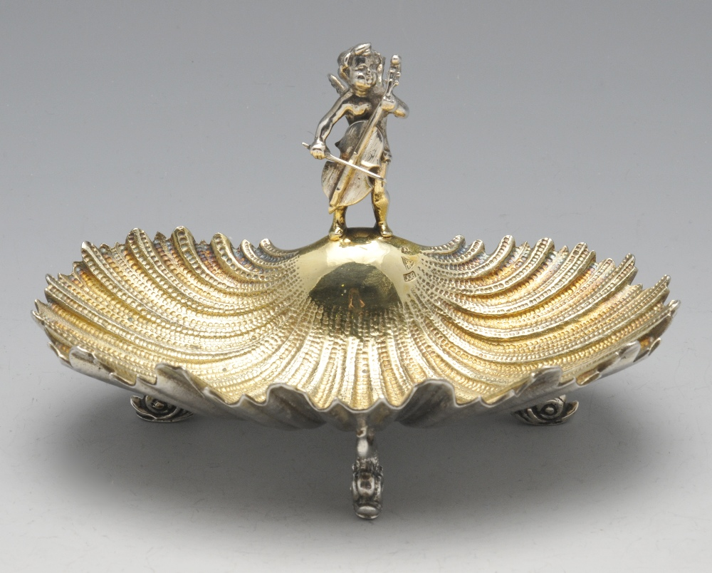Lot 490 - A small continental shell dish raised on three stylised dolphin feet and having a figural mount