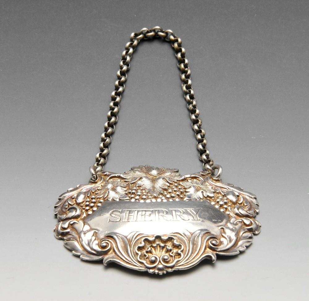 Lot 771 - An early Victorian silver Sherry label with fruiting vine surround and suspended on belcher link