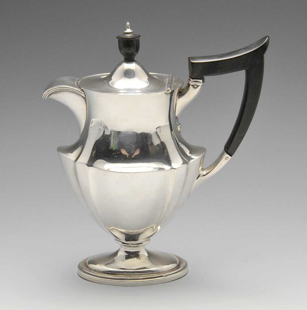 Lot 136 - An Edwardian silver hot water pot, the oval waisted body with fluted corners and ebonised handle and