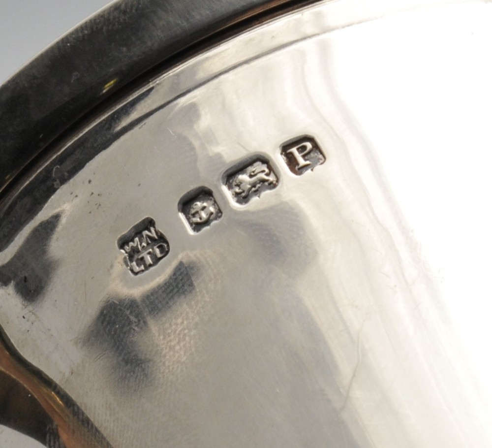 Lot 276 - An Art Deco silver mug, of slight tapered form having accented handle raised upon a stepped foot.