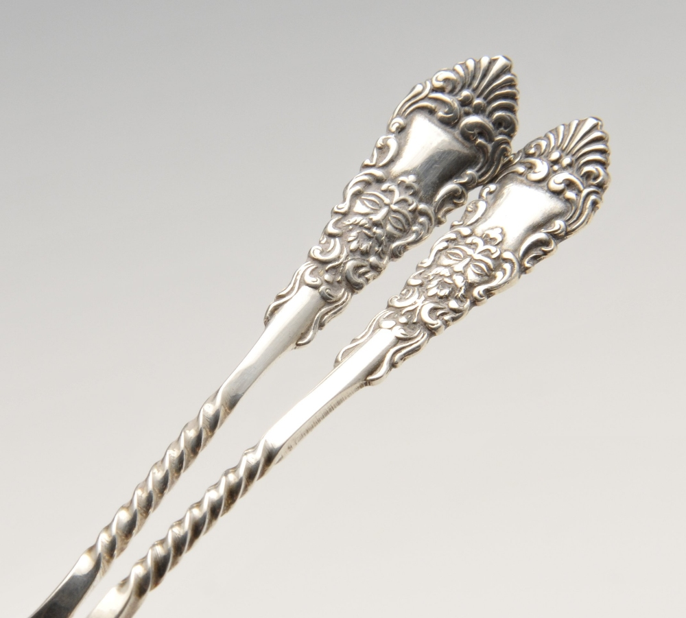 Lot 590 - A cased set of six Edwardian silver teaspoons and sugar tongs, the spoons having mask and foliate