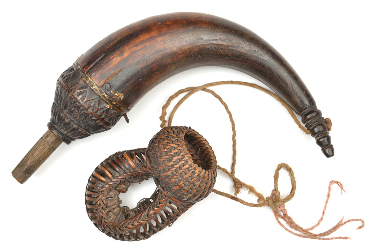 Lot 24 - A Cambodian powder horn. Probably 19th century, 26cms, swollen top carved with lotus leaves,