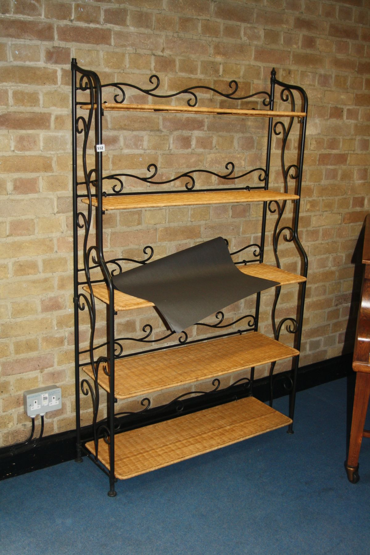 Lot 552 - A METAL AND WICKER CASCADE BOOKCASE, with five shelves standing, 162cm high 97cm wide