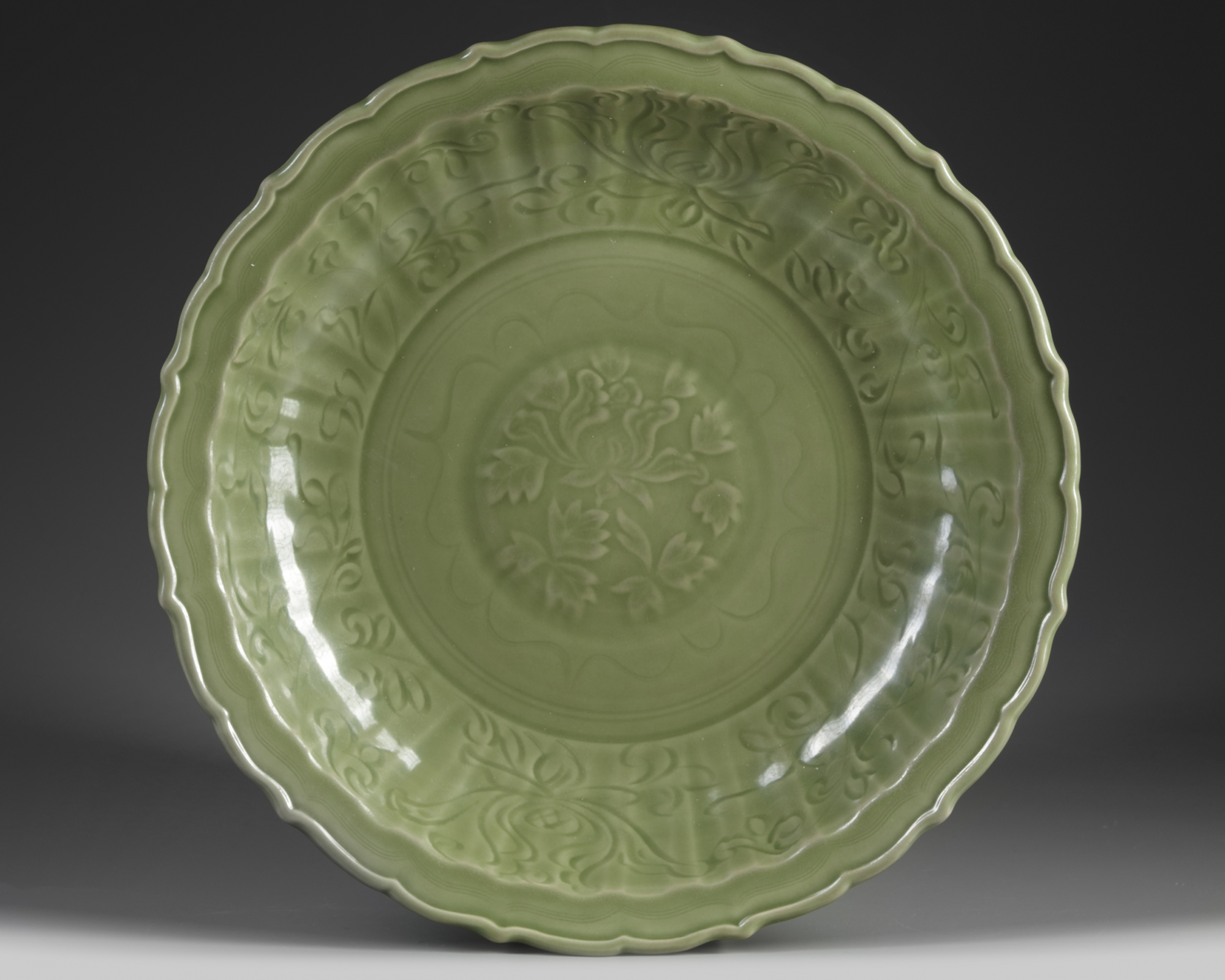 Lot 57 - A Chinese Longquan-celadon-glazed 'lotus' barbed-rim charger