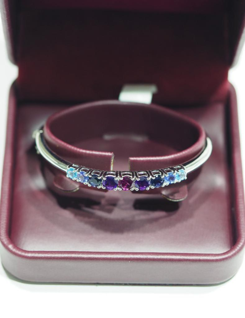 Lot 40 - Sterling Silver Bangle with Garnet, Amethyst, Blue Topaz, Tanzanite and Iolite. Appraised $450