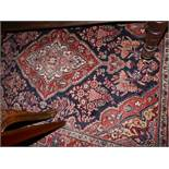 A fine Sarouk rug, with central floral medallion, on a red and blue ground, contained by floral