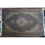 A part silk Tabriz rug, with floral medallion, on a blue and beige ground, contained by floral