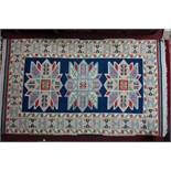 A Kazak rug with triple geometric medallion, on a blue ground, contained by geometric border on a
