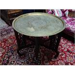An Islamic brass tray on folding hardwood stand, the tray engraved with scrolling foliage, geometric