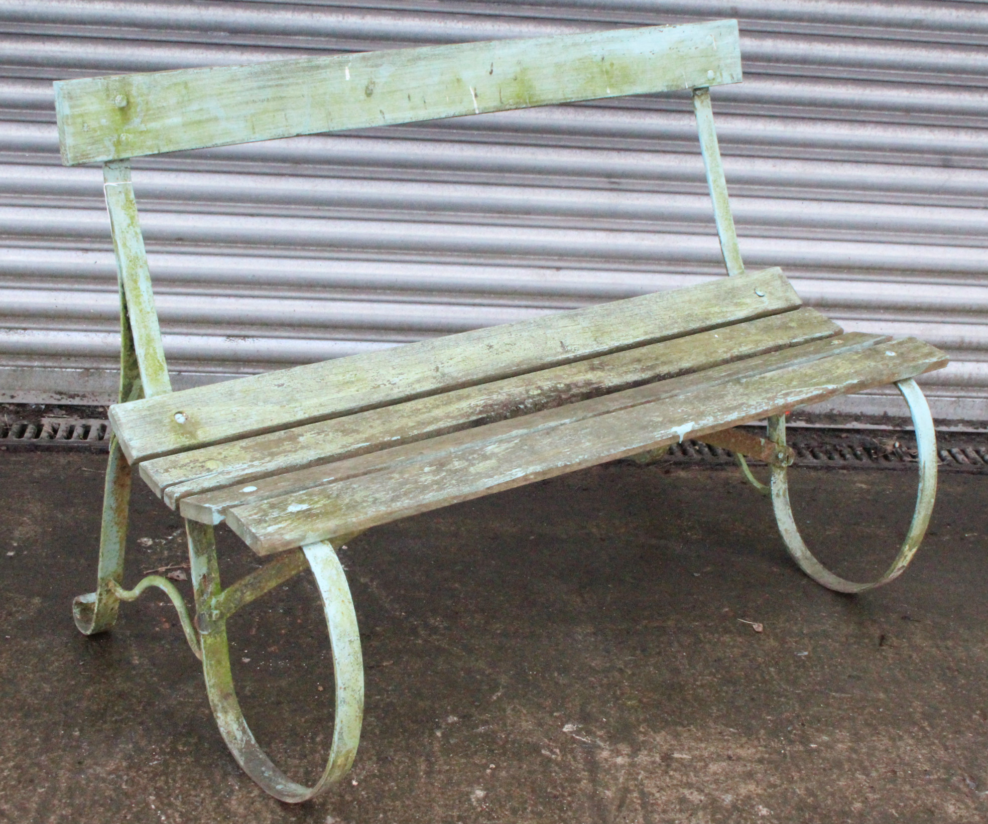 Lot 229 - A late 19th/early 20th century green painted teak & wrought-iron garden bench on scroll-shaped end