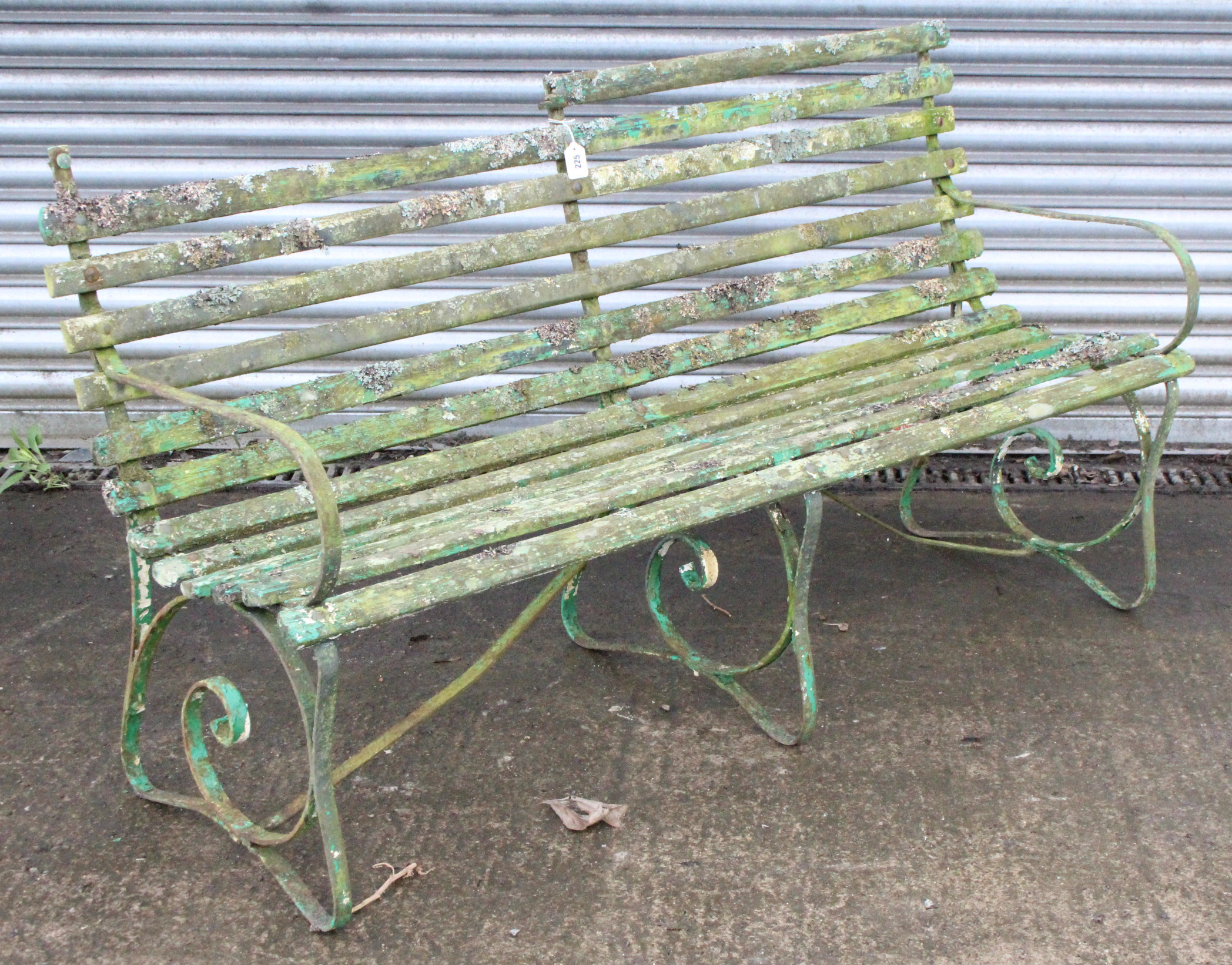 Lot 225 - A late 19th/early 20th century green painted teak & iron garden bench on three scroll supports (