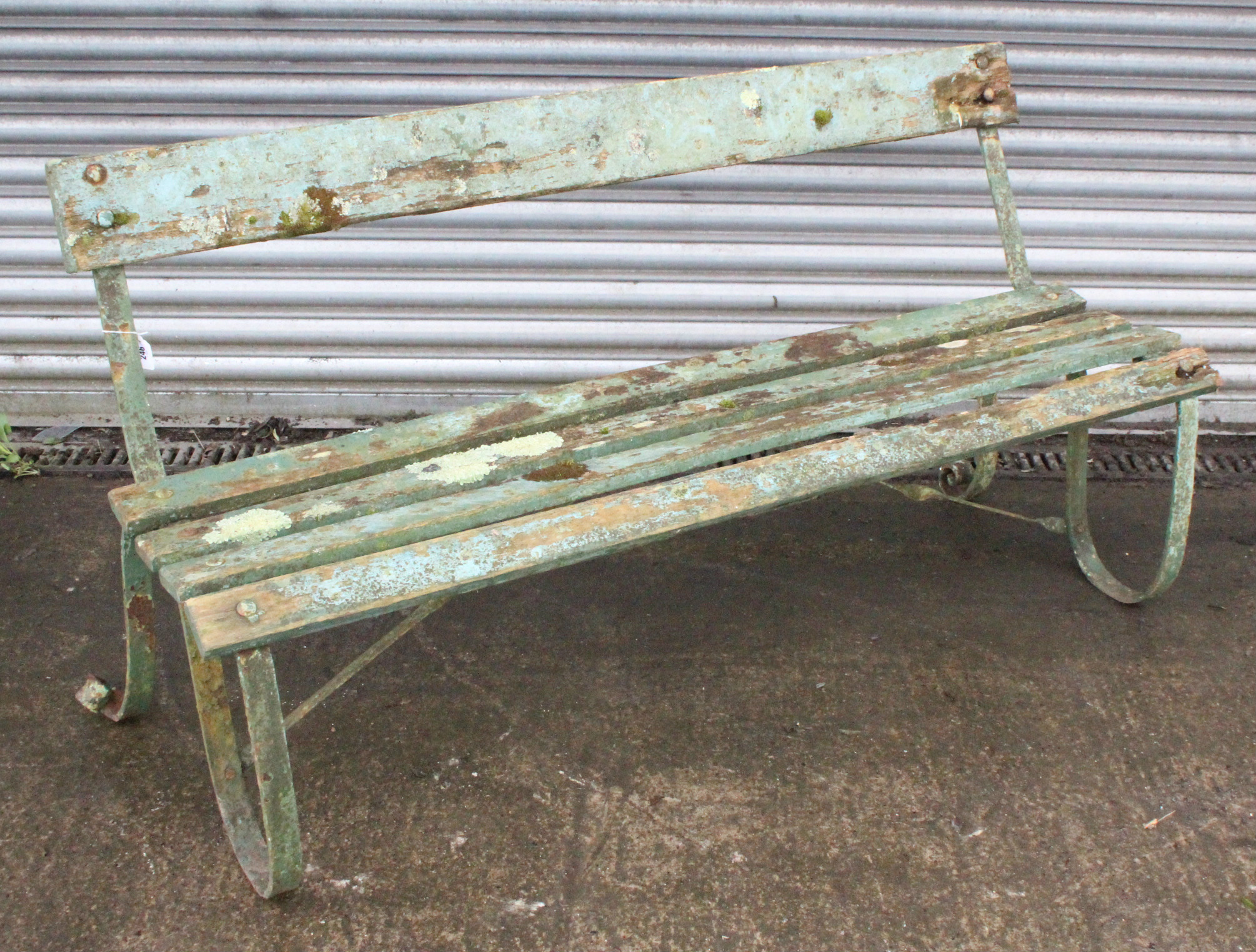 Lot 246 - A late 19th/early 20th century green painted teak & wrought-iron garden bench on scroll-shaped end