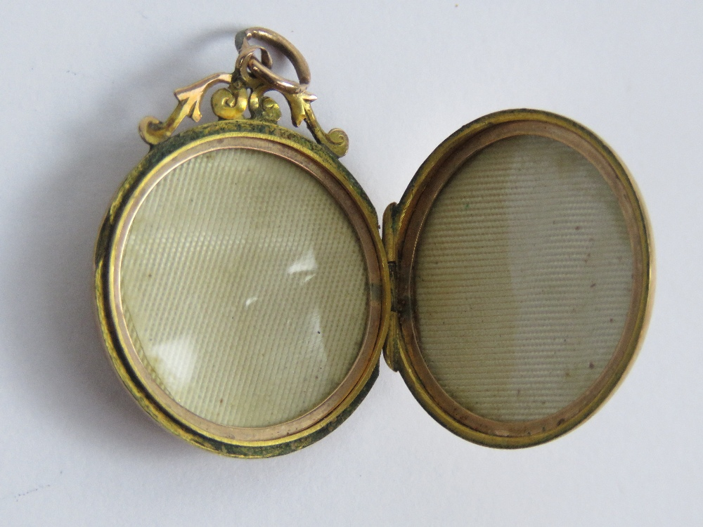 Lot 113 - A 9ct gold locket of circular form having floral engraving to front and back, slightly a/f,