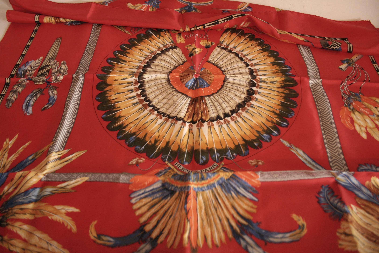 """Lot 32 - Carré en soie HERMES, rouge au motif de coiffe de chef Indien """"BRAZIL"""" - HERMES silk [...]"""