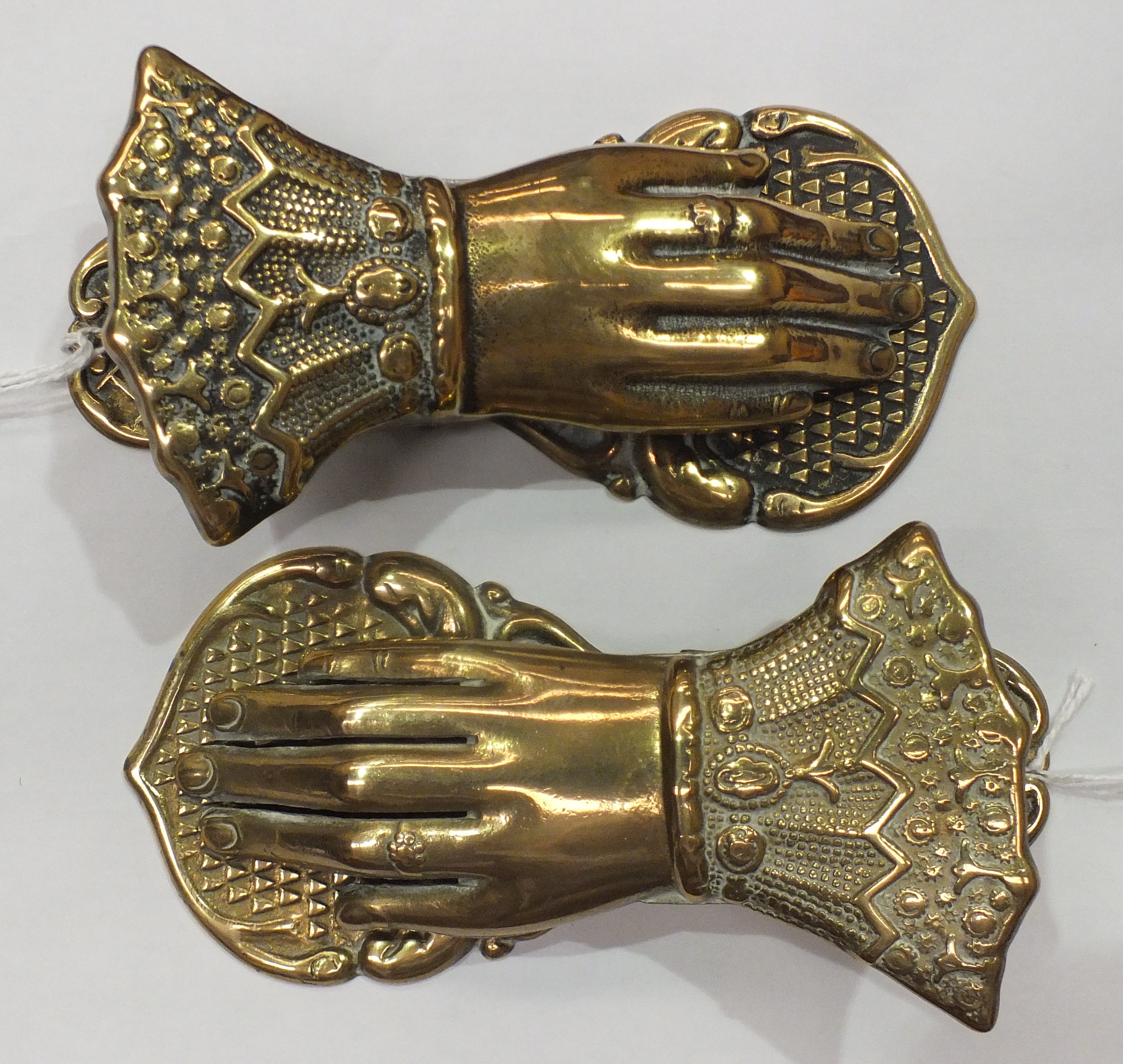 Lot 215 - Two brass paper tidies, each in the form of a human hand, 13cm long.