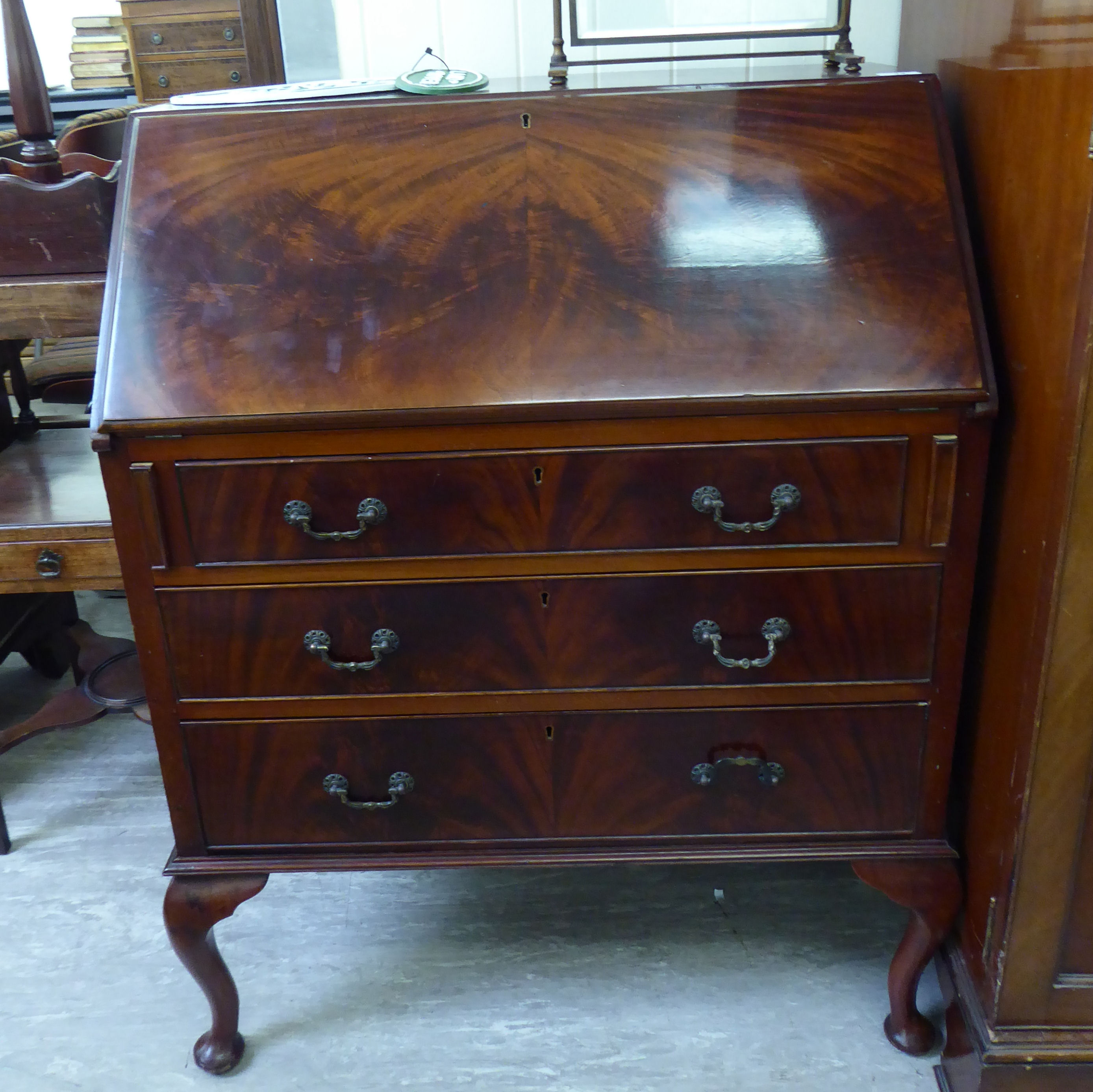 Lot 44 - A 1930s mahogany bureau with a fall flap and three long drawers,