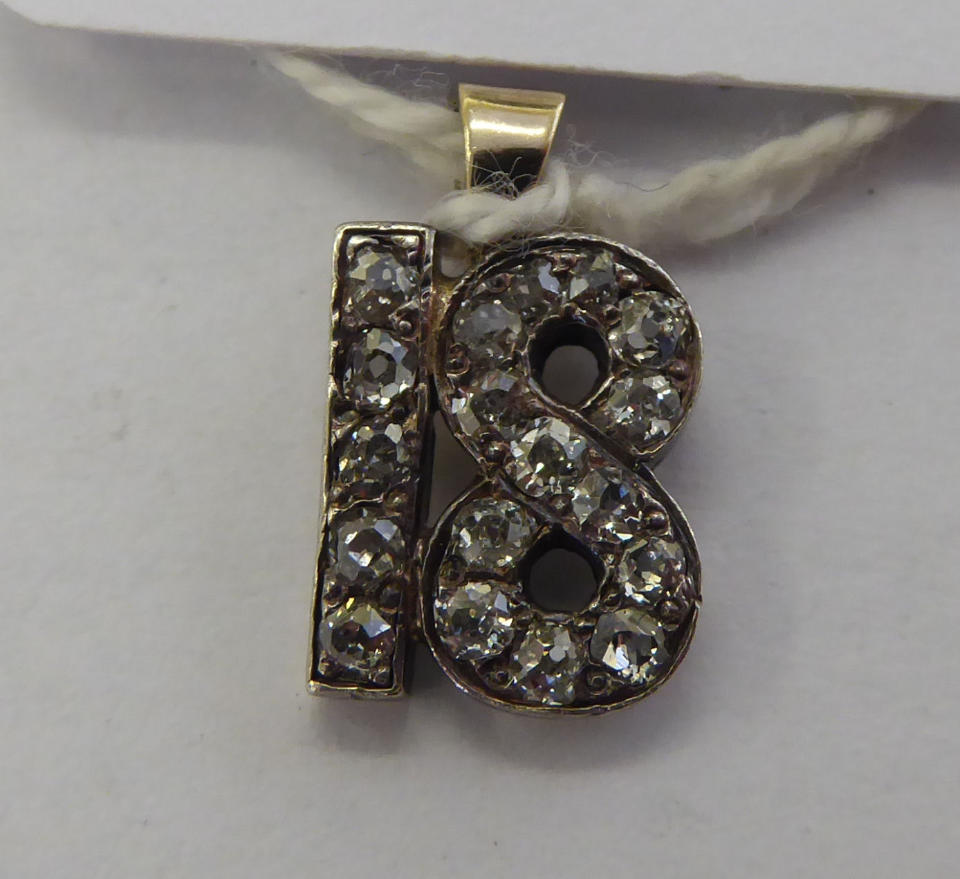 Lot 19 - An early 20thC yellow metal diamond set pendant '18' 11