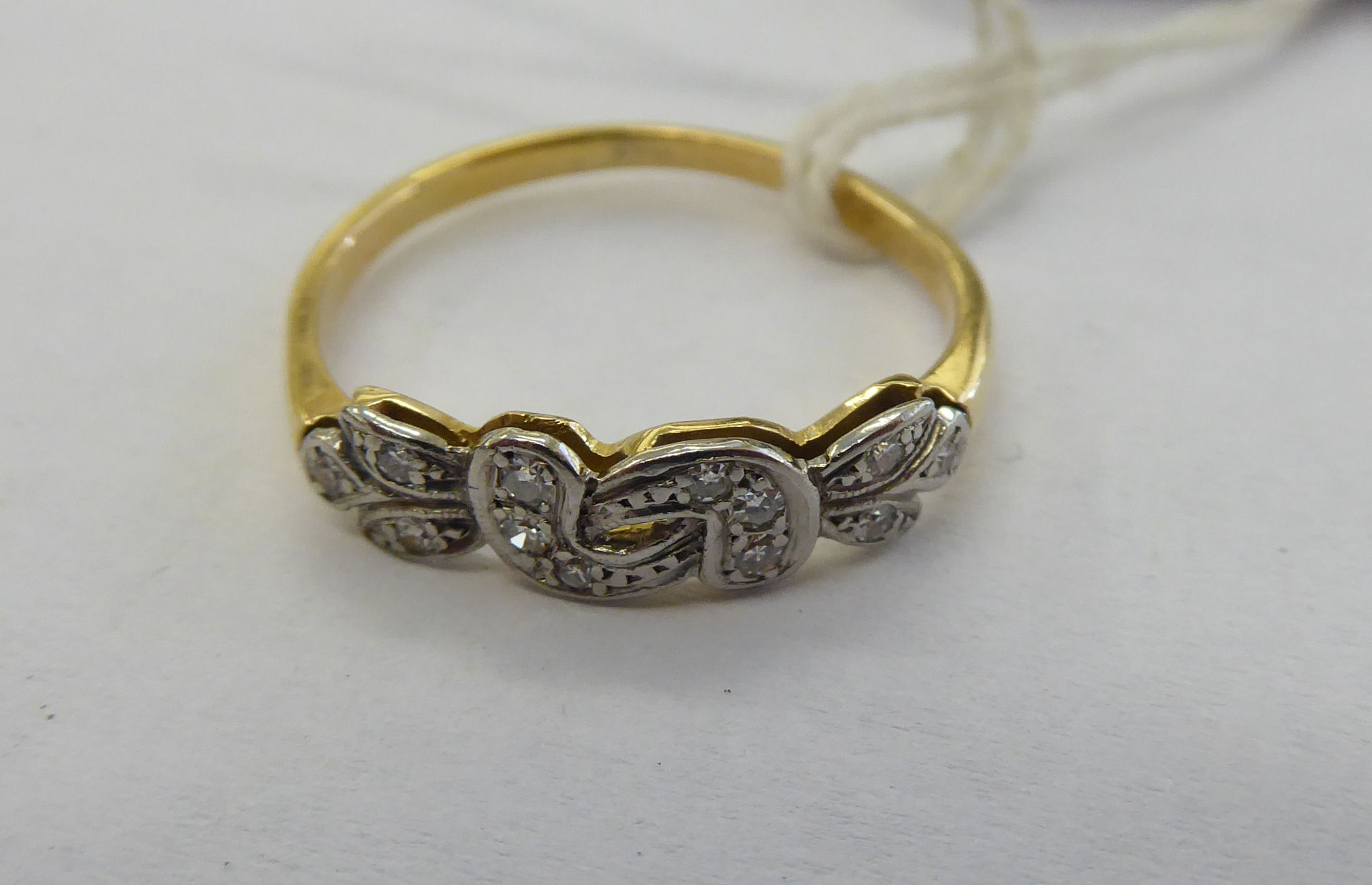 Lot 9 - An 18ct gold ring with a fancy crossover bezel,