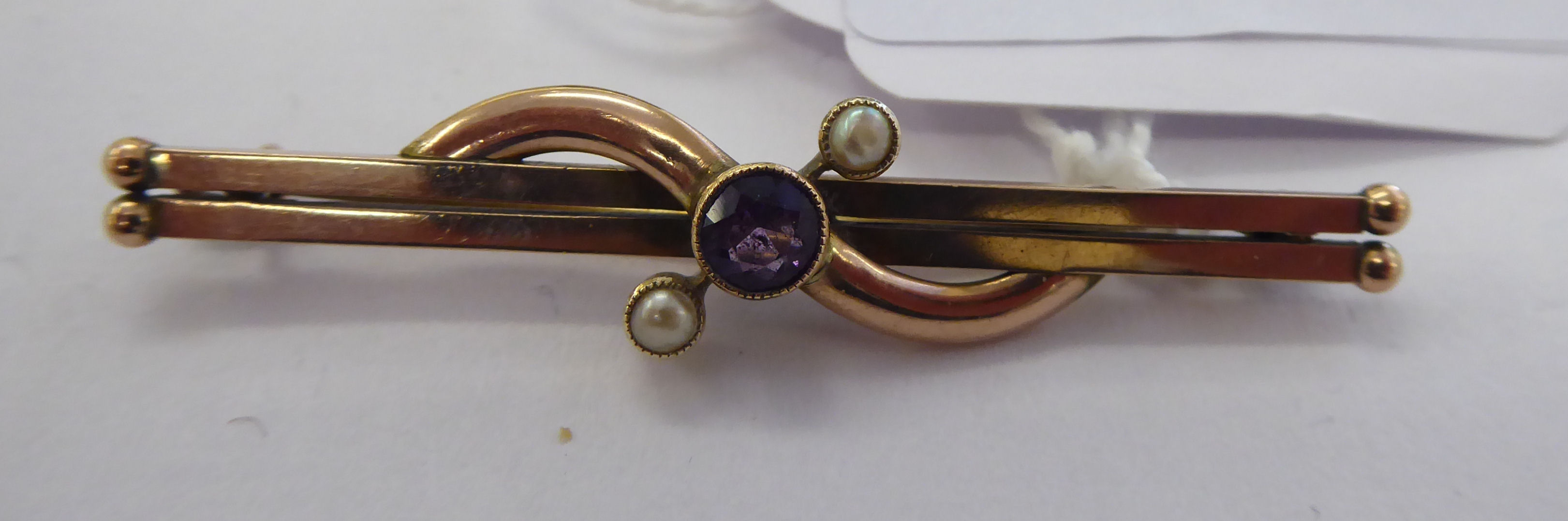 Lot 36 - An 'antique' gold coloured metal amethyst and seed pearl set bar brooch 11