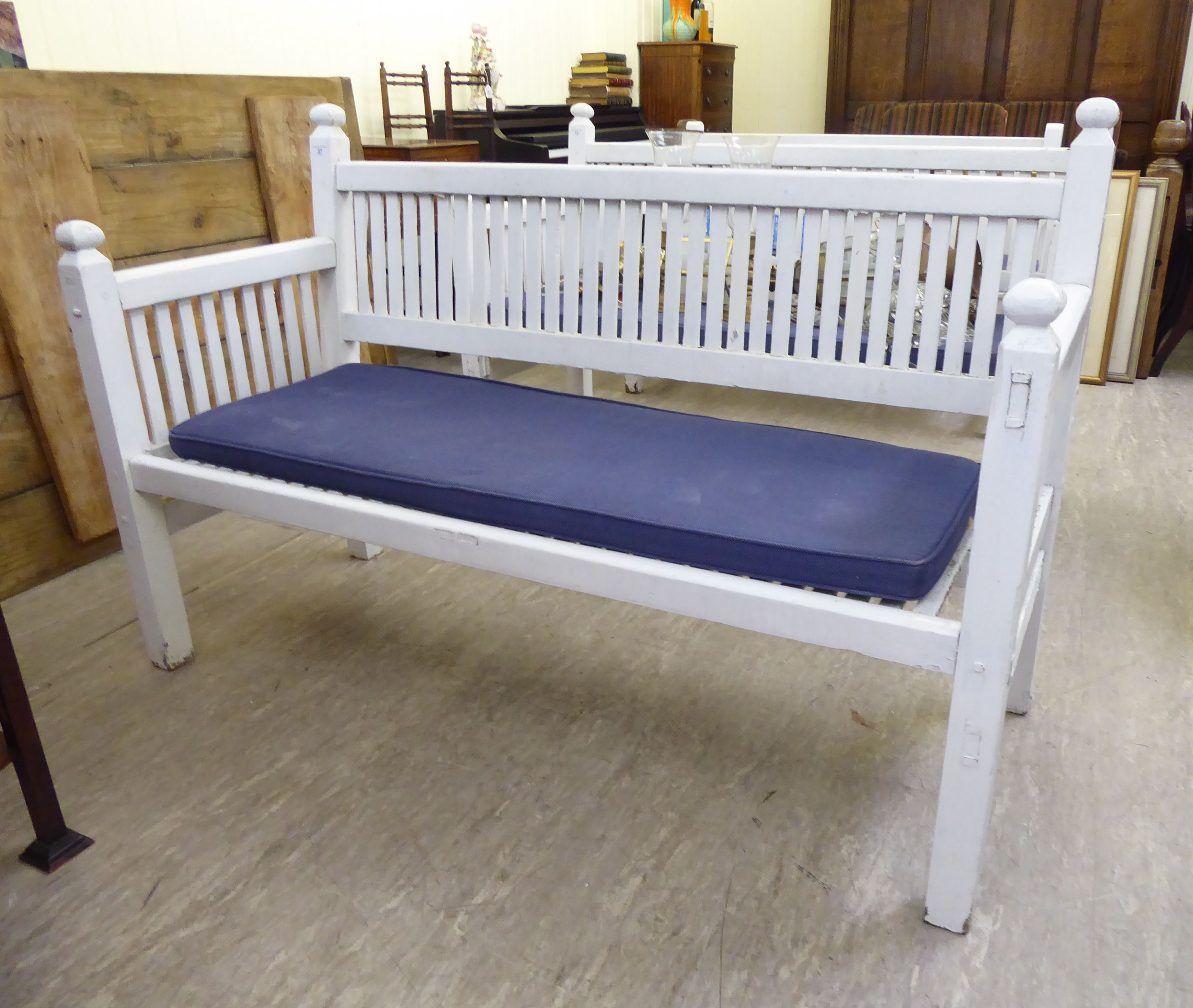 Lot 37 - A modern white painted garden bench of slatted construction,