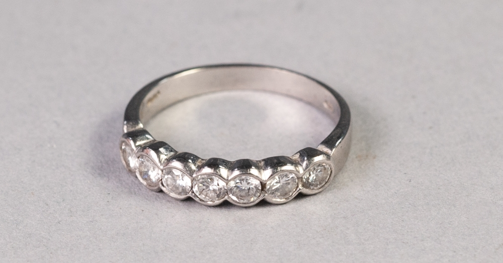Lot 158 - WHITE METAL RING COLLET SET WITH A ROW OF SEVEN SMALL DIAMONDS GRADUATING FROM THE CENTRE, 3.6
