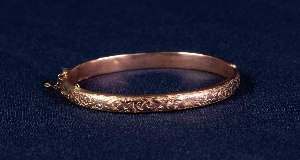 Lot 60 - LATE VICTORIAN 9ct GOLD HOLLOW BANGLE, hinge opening with foliate scroll engraved top, Birmingham