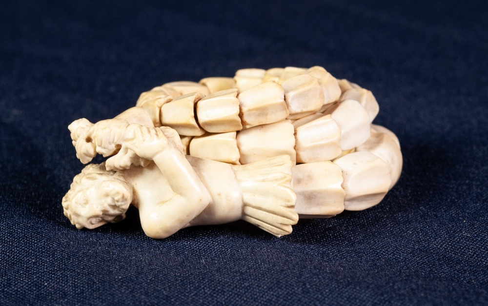 Lot 100 - AN ANTIQUE EUROPEAN CARVED SECTIONAL IVORY SPRUNG BANGLE, with bell flower pattern tapering link