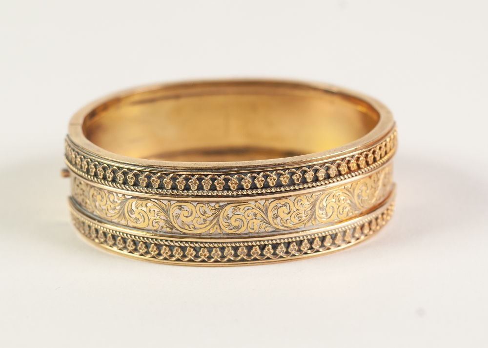VICTORIAN GOLD COLOURED METAL HINGE OPENING BROAD BANGLE, the top finely pierced with foliate
