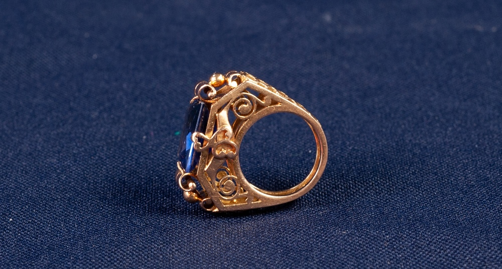 GOLD AND SYNTHETIC SAPPHIRE DRESS RING with an emerald cut sapphire, in a four claw setting with - Image 2 of 2