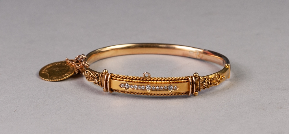 Lot 73 - VICTORIAN 15ct GOLD HOLLOW HINGE OPENING BANGLE, the fancy filigree decorative top set with a row of