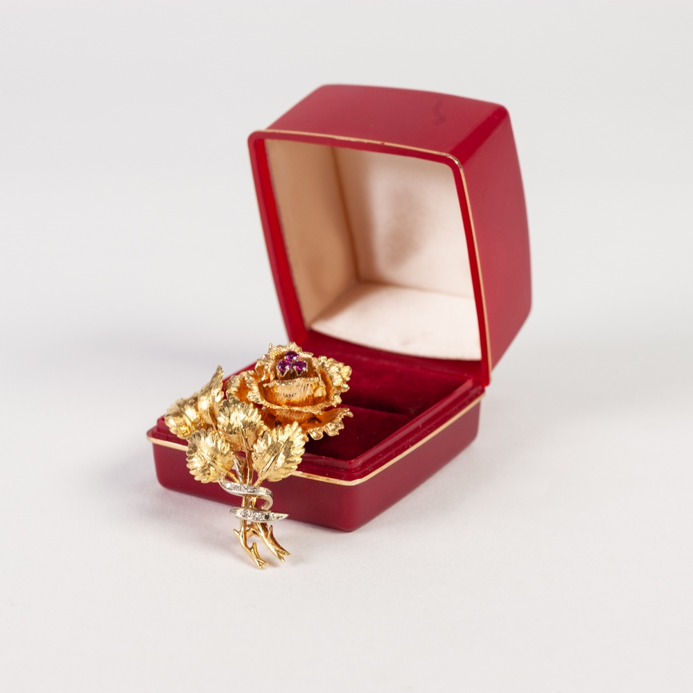 Lot 153 - 9ct GOLD ROSE SPRAY BROOCH, the bloom centred by three rubies, the stems tied by two white gold