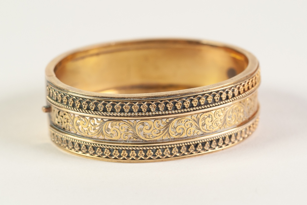 Lot 61 - VICTORIAN GOLD COLOURED METAL HINGE OPENING BROAD BANGLE, the top finely pierced with foliate