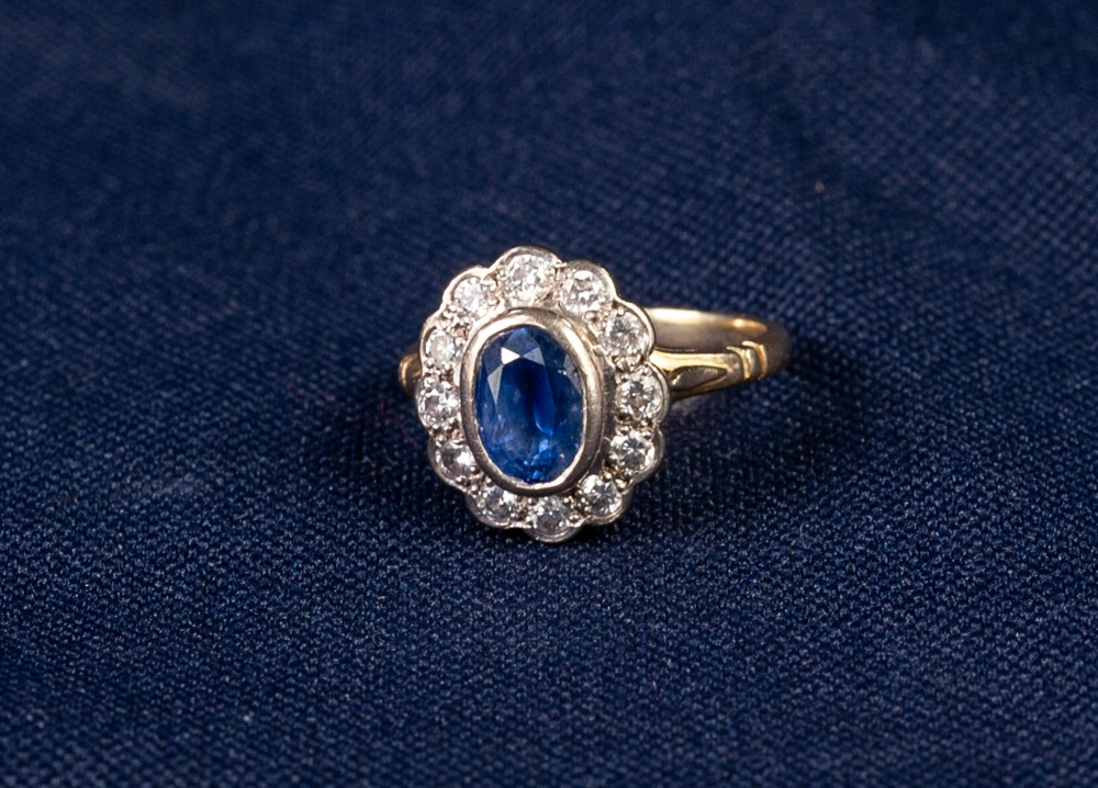 Lot 177 - 18ct GOLD, SAPPHIRE AND DIAMOND CLUSTER RING, collet set with an oval sapphire and surround of