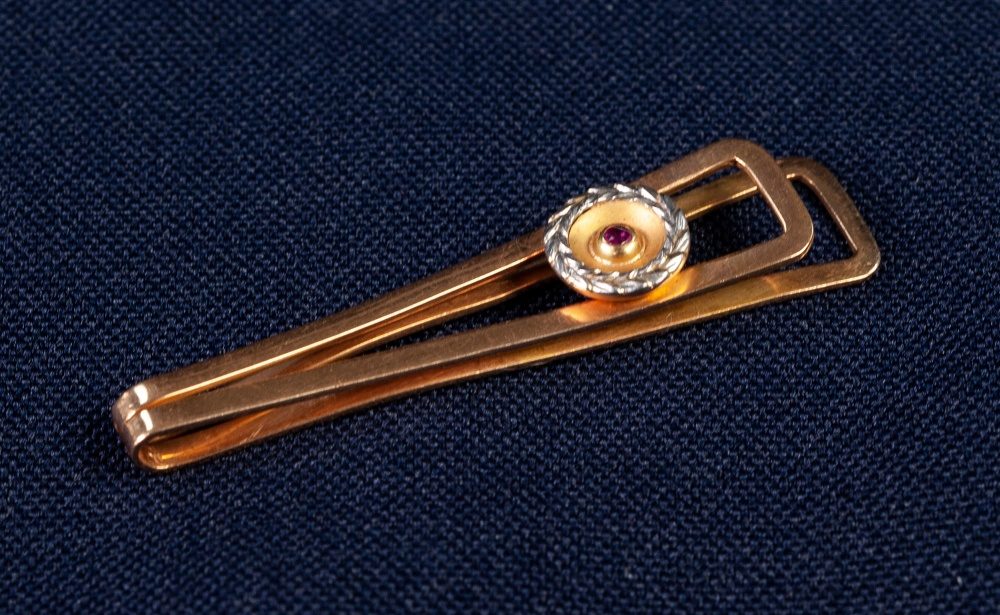 Lot 94 - GOLD COLOURED METAL TIE CLIP with applied disc with white wreath border and centre tiny collet set