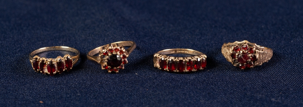Lot 111 - FOUR 9ct GOLD GARNET SET DRESS RINGS, 11.6 gms all in gross (4)