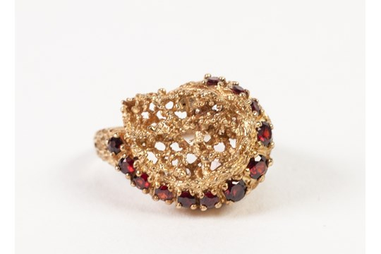 Lot 148 - 9ct GOLD PIERCED NUGGET PATTERN COCKTAIL RING, set with a curved row of twelve small rubies, 6.5gms,