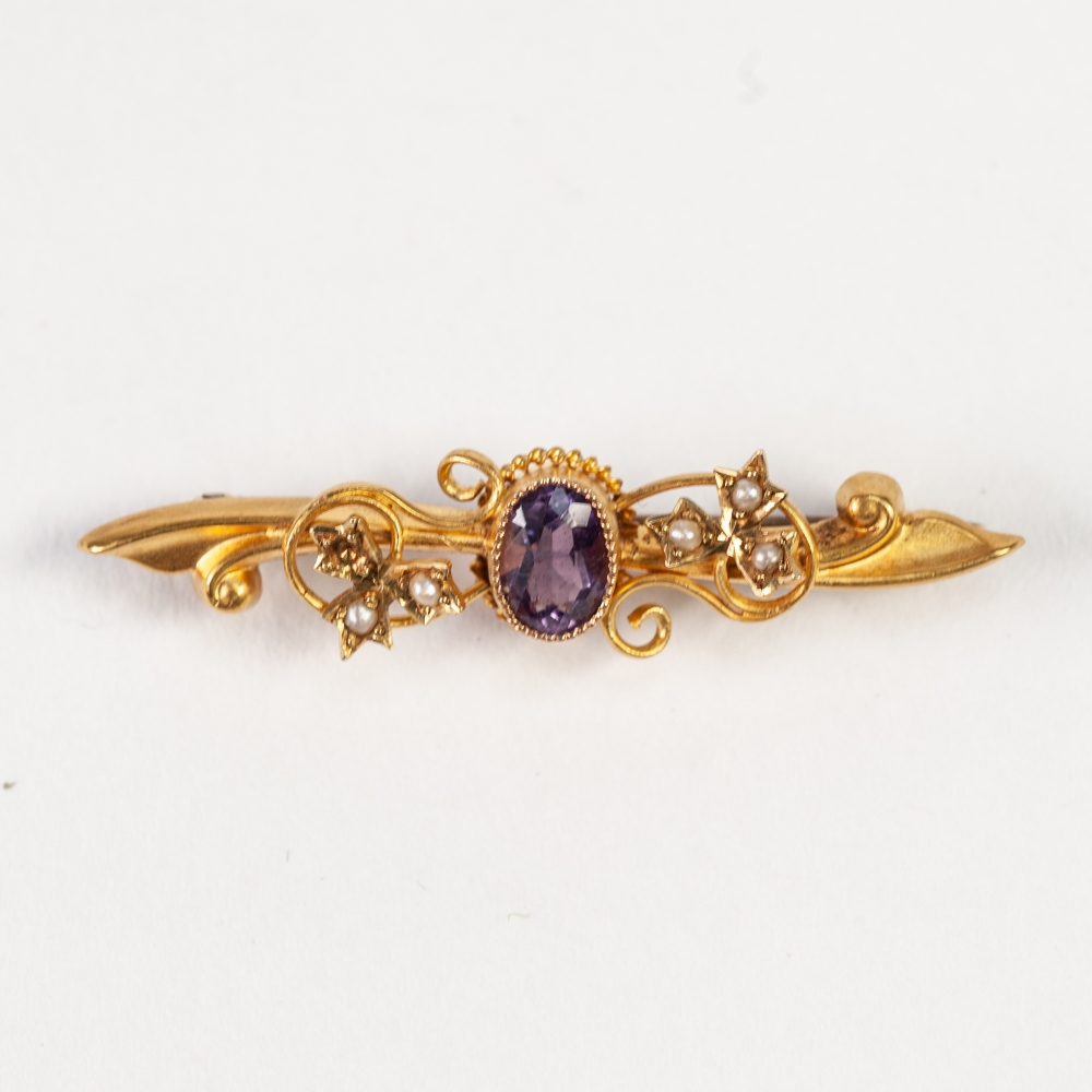 Lot 137 - AN EDWARDIAN 15ct GOLD FOLIATE SCROLL BAR BROOCH, collet set with a centre oval amethyst, and two