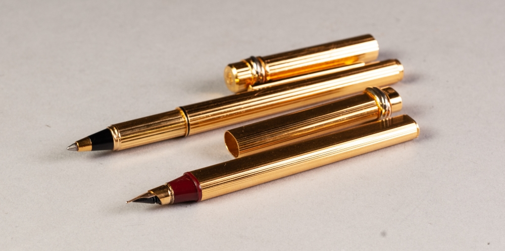 Lot 52 - A MATCHED PAIR OF MODERN CARTIER (PARIS) GOLD PLATED FOUNTAIN AND BALLPOINT PENS, serial numbers