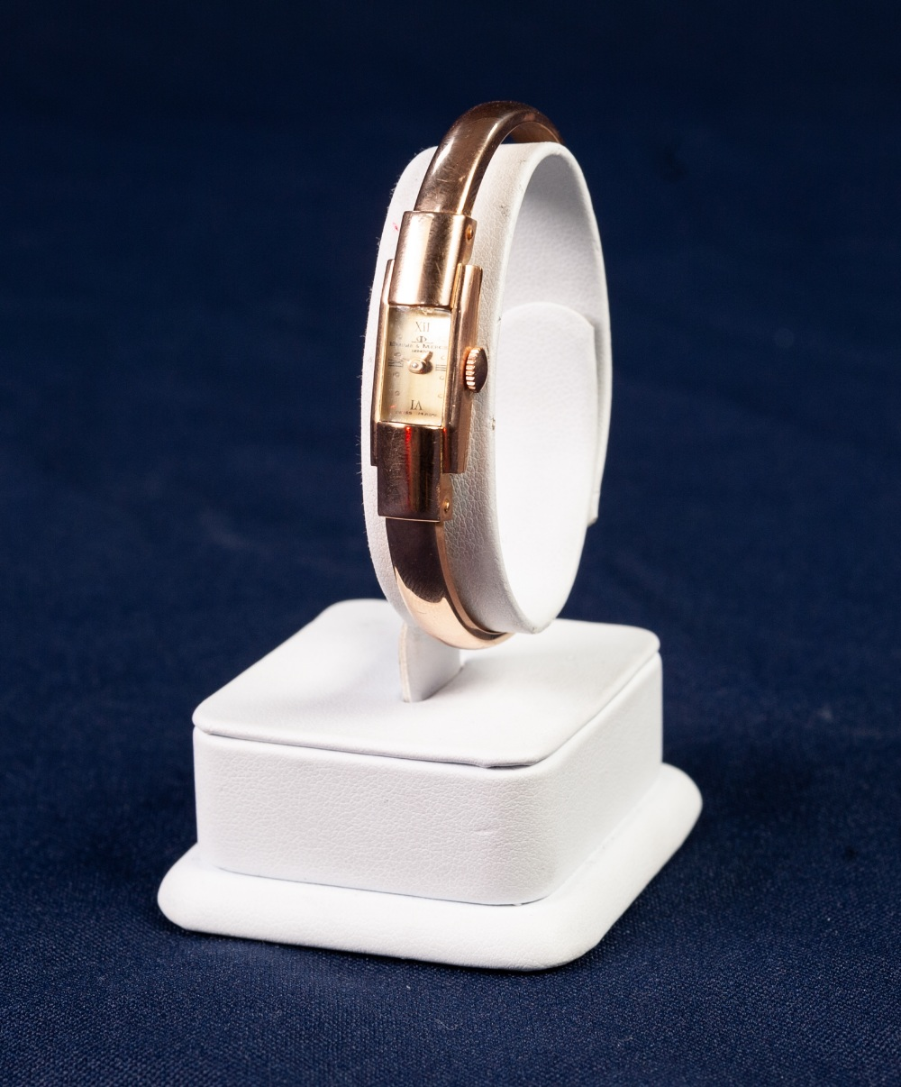 Lot 21 - LADY'S BAUME & MERCIER, GENEVE, 18ct GOLD SPRUNG BANGLE WATCH with mechanical movement, tiny