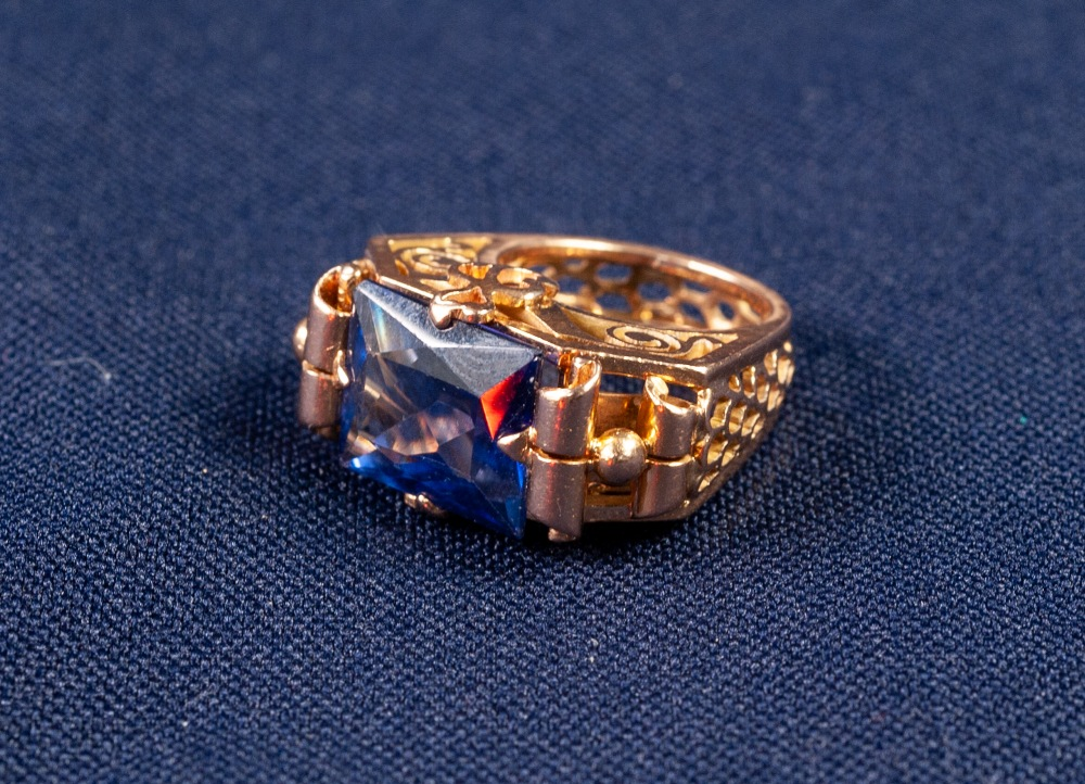 GOLD AND SYNTHETIC SAPPHIRE DRESS RING with an emerald cut sapphire, in a four claw setting with