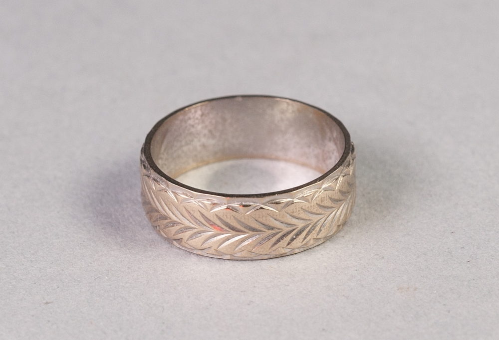 Lot 154 - 18ct WHITE GOLD BROAD WEDDING RING with foliate engraving, London 1977, 5.3 gms, ring size N/O