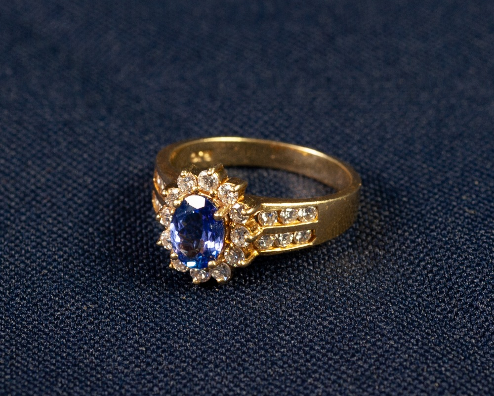 Lot 171 - 18ct GOLD TANZANITE AND DIAMOND CLUSTER RING, set with an oval tantanzite of medium deep bluish