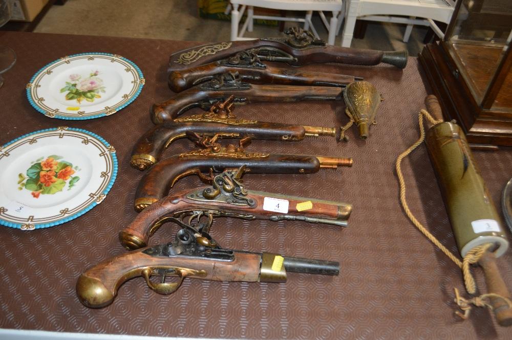 Lot 4 - Seven replica pistols and a powder flask