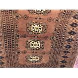 CAUCASIAN RUG ON A SALMON GROUND HAVING SEVEN CENTRAL MEDALLIONS 93CM X 150CM APPROX