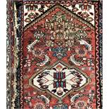 EARLY 20TH CENTURY CAUCASIAN RUG HAVING CENTRAL MEDALLION ON A RED AND BLUE GROUND 83CM X 130CM