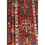 CAUCASIAN RUG ON A RED GROUND 74CM X 300CM APPROX