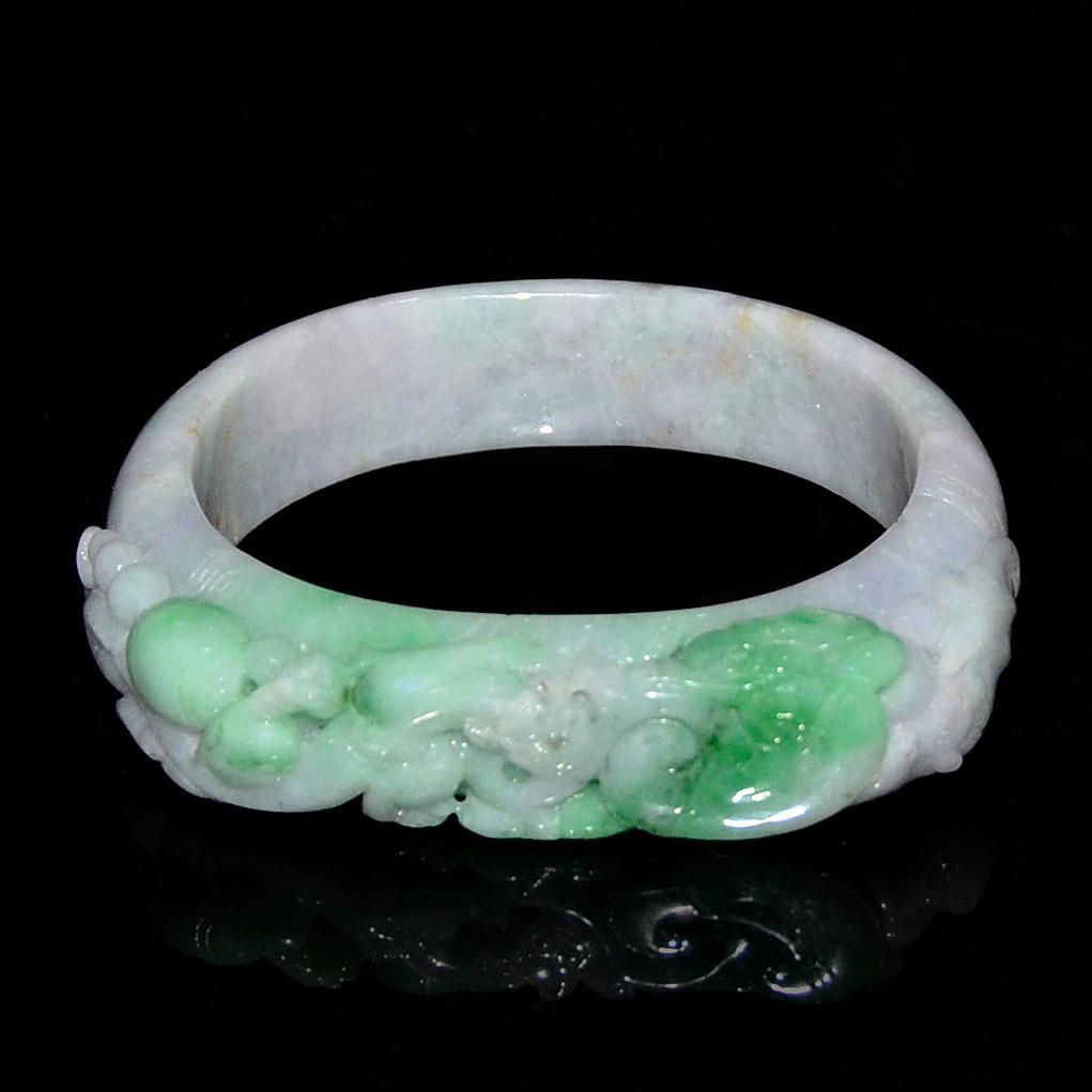 Lot 16 - 翠玉浮雕福壽如意手鐲 Jadeite Bracelet Carved with Auspicious Ruyi and Peach for Longevity Diameter: 2⅝ in (6.7