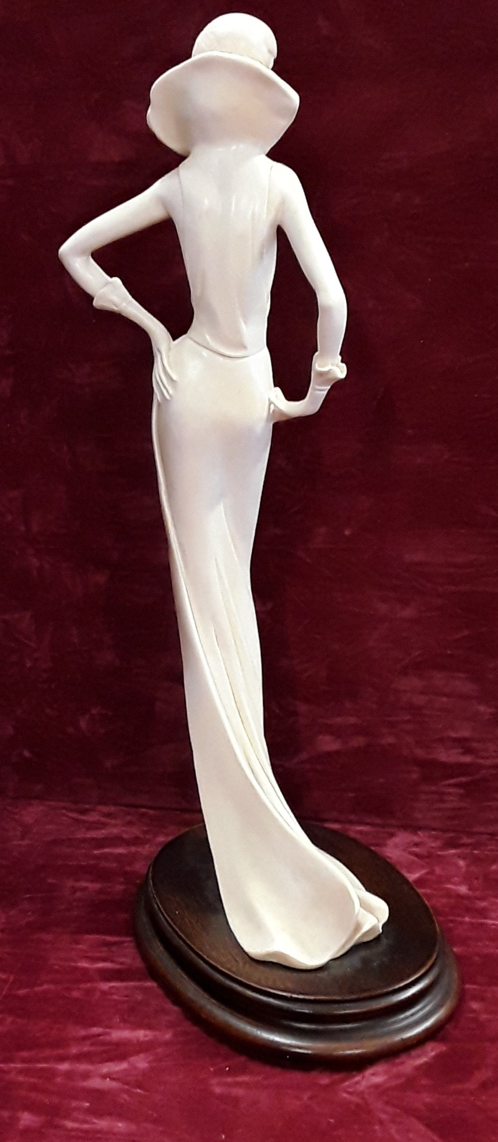 Lot 4 - A signed Amilcare Santini faux ivory figure of an elegant lady on an oak base.