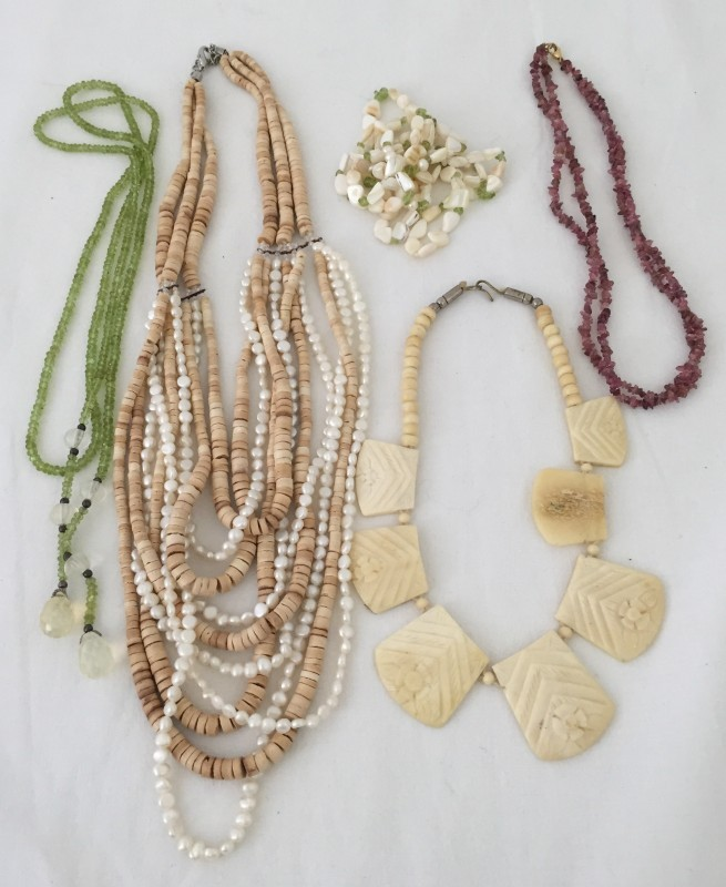 Lot 1011 - 5 necklaces featuring stones, shells and carved bone.